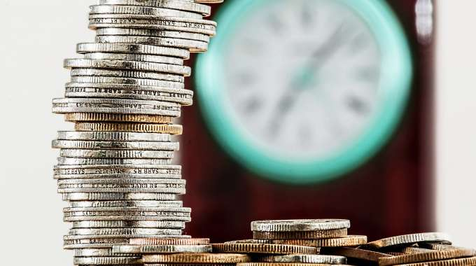 Coins next to clock-- Time is money, especially when it comes to saving and compound interest.