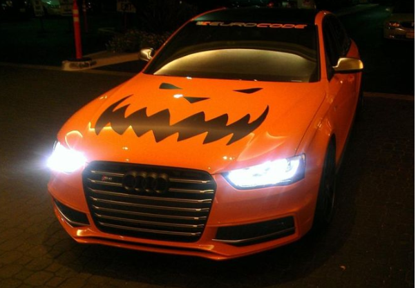 Orange Audi with pumpkin design on the hood