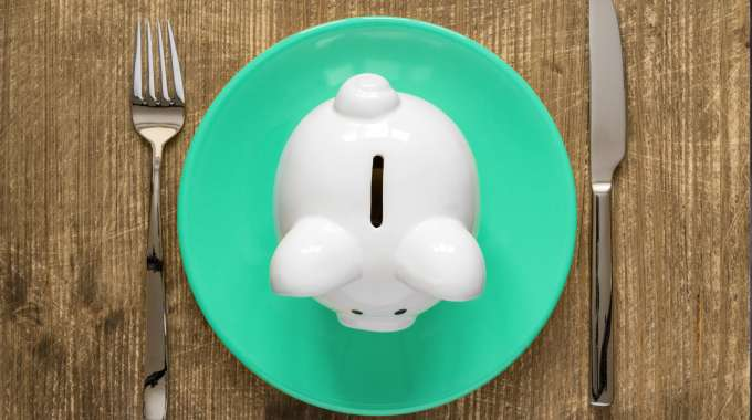 Piggy bank on a lunch plate signifies eating lunch on a budget