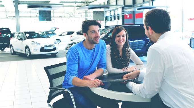 man and woman negotiating with car dealer in the showroom