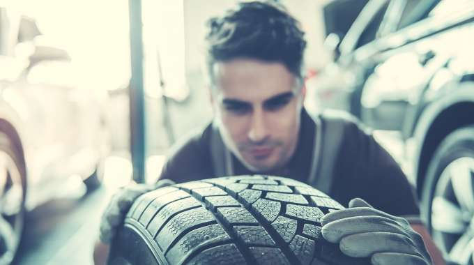 Man inspecting the tread of a new tire