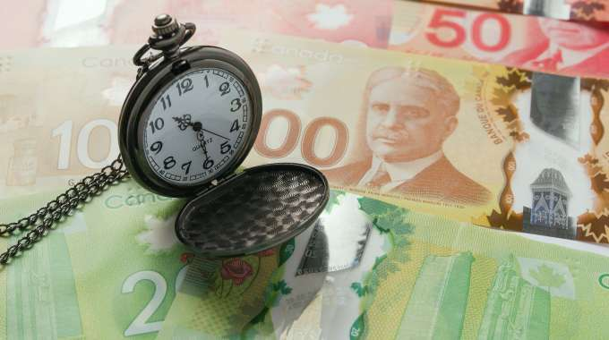 Pocket watch on top of Canadian cash