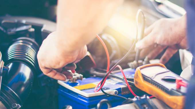 Mechanic inspects battery with handheld multimeter (voltmeter)
