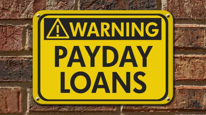 Warning sign payday loans on a brick wall