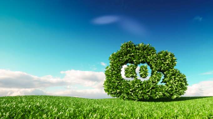 CO2 letters trimmed on hedges in a green field, signifying Carbon Taxes and the environment
