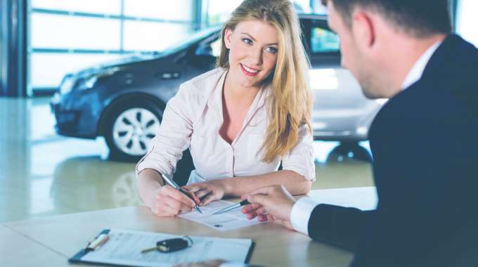 Woman refinancing car loan for a better rate and monthly payment