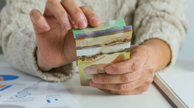 Person counting canadian money that they've saved through good saving habits