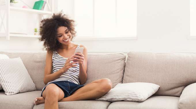 Person relaxing on couch searching for easy ways to improve their personal finances