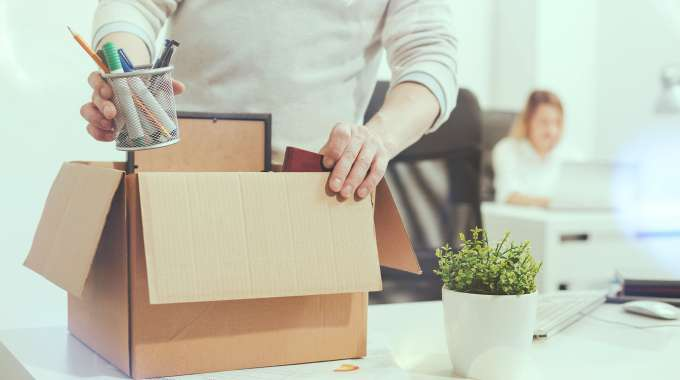 Person fills a box with personal belongings after losing their job